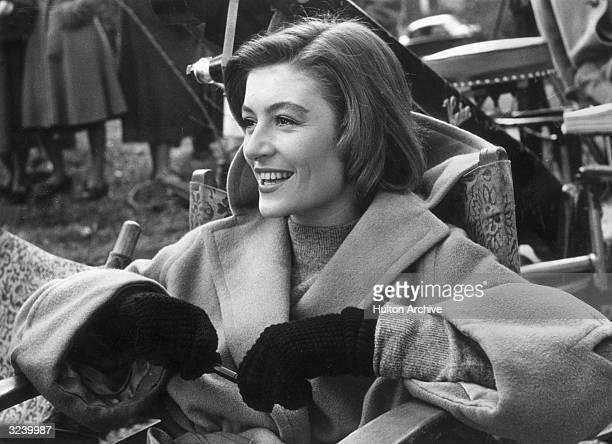 French actor Anouk Aimee, wearing a camel-hair overcoat and gloves, laughs while sitting in a folding chair on a film set.