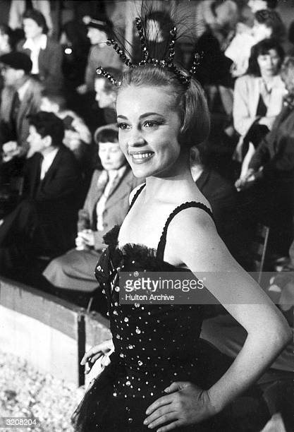 French actor Jeanne Moreau wears a black costume with rhinestones and a feathered tiara while standing before a crowd