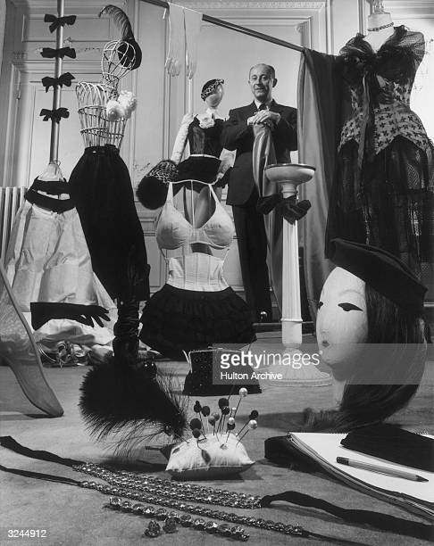 French fashion designer Christian Dior standing in a showroom with samples of his design accessories for women including hats hat pins gloves muffs...