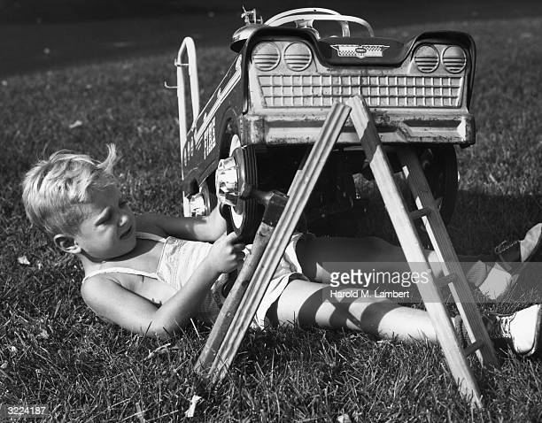 Fulllength image of a young boy lying on the grass under his toy fire truck working on a wheel with a wrench