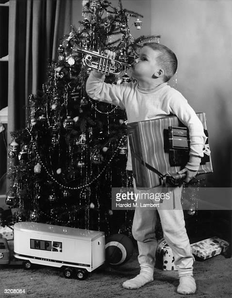 Fulllength image of a young boy standing in front of a Christmas tree holding an armful of wrapped presents and playing a toy trumpet There is a toy...