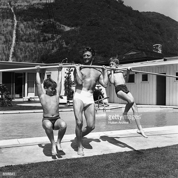 Full-length image of American actor Kirk Douglas using a pole to lift his sons, Joel and Michael, on the deck of a swimming pool.