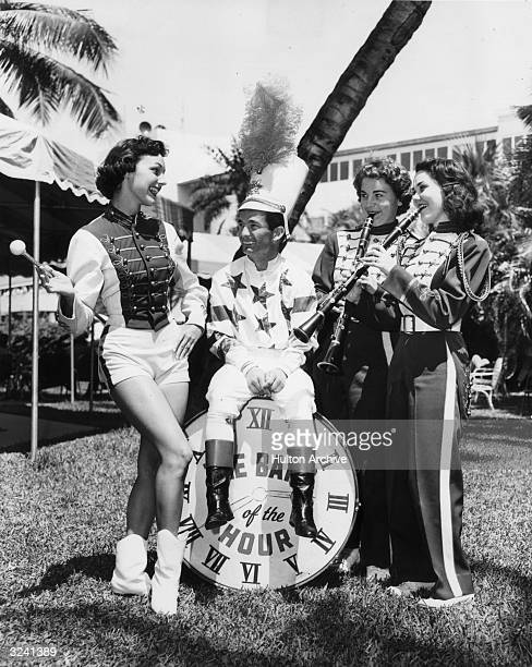 Fulllength image of American jockey Willie Shoemaker sitting outdoors on a large drum surrounded by three University of Miami Marching Band...