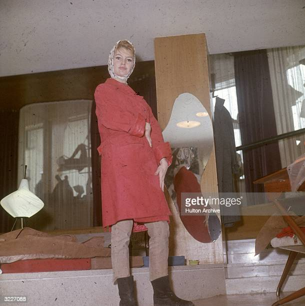Fulllength image of French actor Brigitte Bardot wearing a red suede coat beige cords and a silk scarf over her head