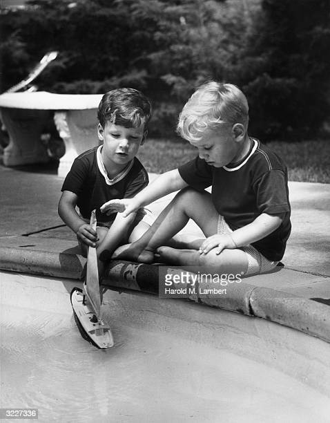 Fulllength image of two young boys sitting on the edge of a stone pool putting a toy sailboat in the water