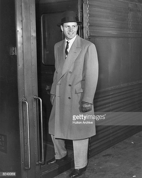 Fulllength portrait of a man wearing an overcoat a hat and leather gloves boarding a train