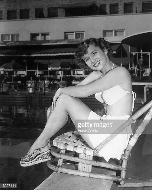 Fulllength portrait of American actor Debbie Reynolds smiling and sitting in a beach chair at the edge of a swimming pool She wears a twopiece...