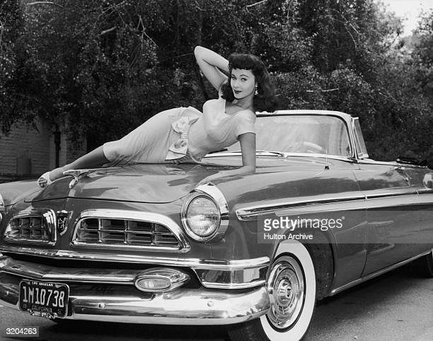 Fulllength portrait of American actor Marla English laying across the hood of a Chrysler convertible Los Angeles California