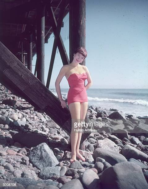 Fulllength portrait of American actor Shirley MacLaine wearing a pink strapless swimsuit standing on the rocks beneath a wooden pier by the seashore