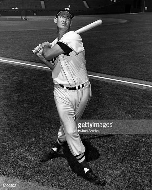Fulllength portrait of American baseball player Ted Williams swinging a bat in Boston Red Sox uniform
