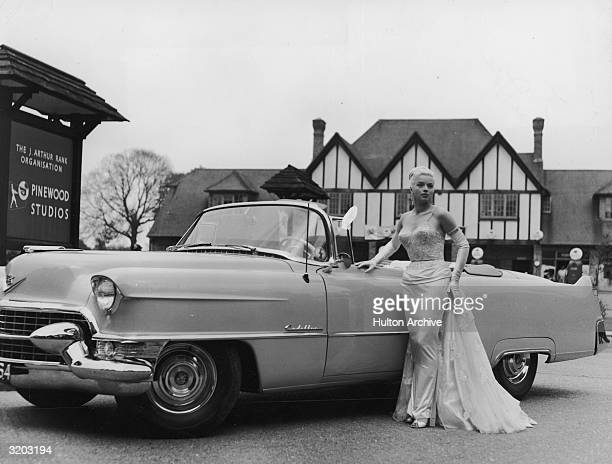 Fulllength portrait of British actor Diana Dors posing next to a Cadillac convertible at the entrance gates of Pinewood Studios Iver Heath...