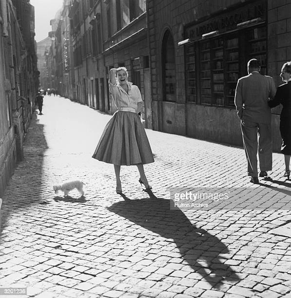 Fulllength portrait of Swedishborn actor Anita Ekberg wearing a full skirt with a striped blouse laughing while posing next to a toy poodle on a...