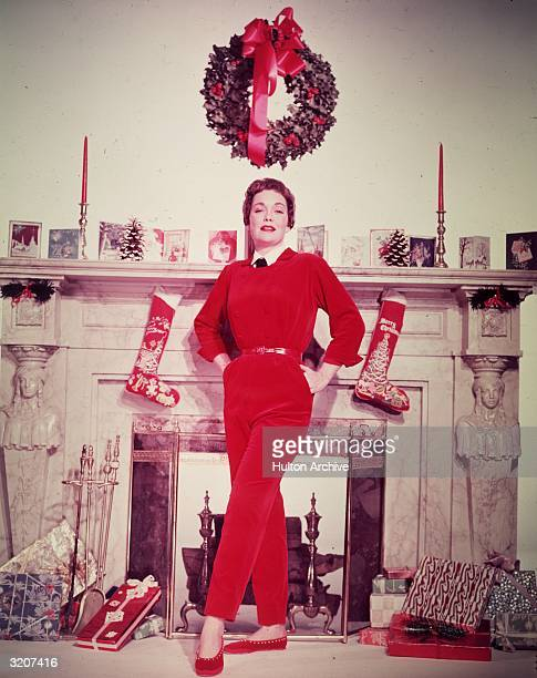 Fulllength promotional portrait of American actor Jane Wyman standing in front of a fireplace decorated with Christmas cards and stockings draped...