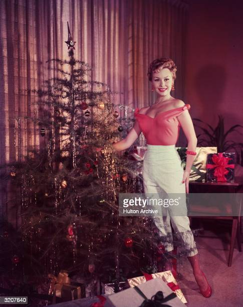 Fulllength promotional portrait of American actor Mitzi Gaynor posing as she decorates a Christmas tree with silver tinsel and ornaments