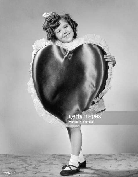 Full-length studio portrait of a young girl with ringlet curls holding a large heart-shaped pillow for Valentine's Day.