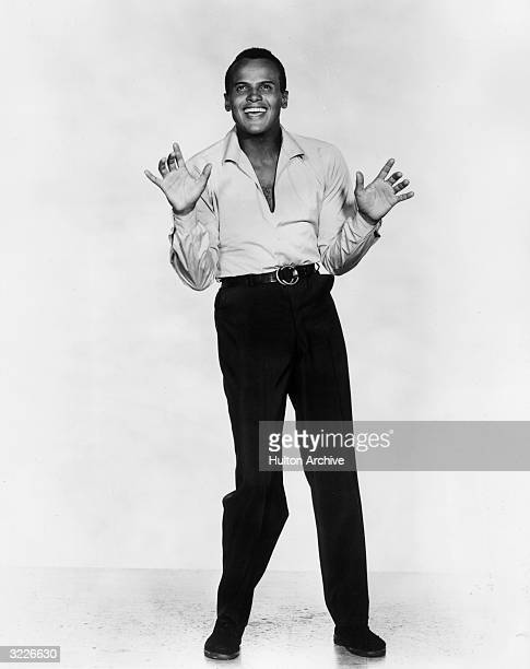 Fulllength studio portrait of American actor and singer Harry Belafonte smiling with his hands raised
