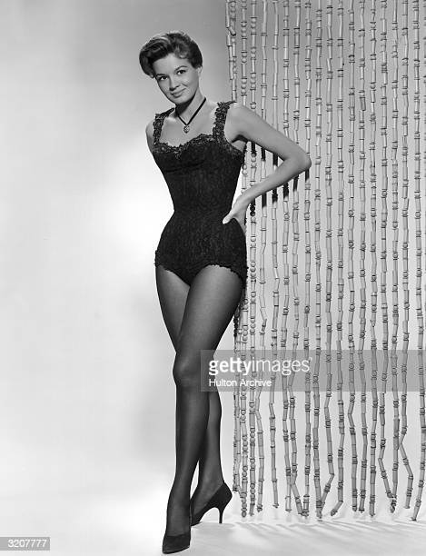 Fulllength studio portrait of American actor Angie Dickinson wearing a lace corset and standing with her hands on her hips in front of a curtain of...