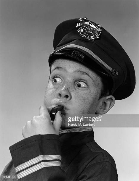 Headshot of a freckled young boy dressed in uniform as a police chief and blowing a whistle