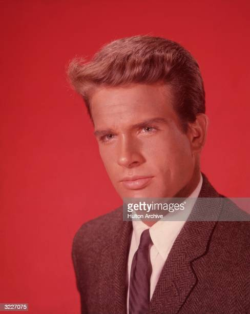 Headshot of American actor Warren Beatty wearing a tweed jacket against a red background
