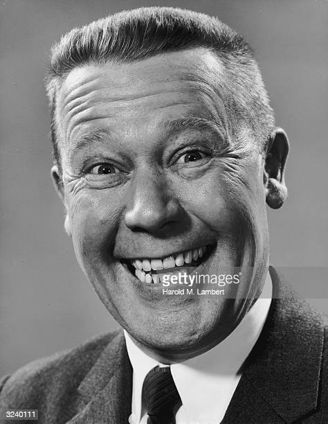 Headshot portrait of a man with a crew cut smiling widely showing all his teeth 1950s