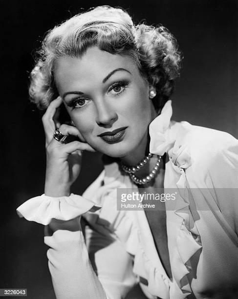 Headshot portrait of actor Eve Arden resting her hand on her face She wears a double strand of pearls and a blouse with ruffled sleeves and a...