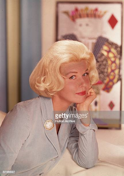 Headshot portrait of American actor and singer Doris Day smiling and leaning on a counter in front of a wall hanging of the king of diamonds 1950s...