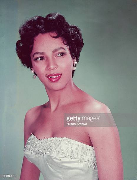 Headshot portrait of American actor Dorothy Dandridge wearing a white strapless dress with a beaded bodice looking to the side