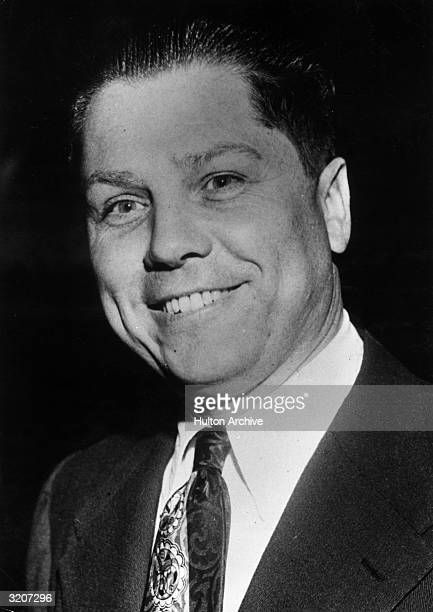 Headshot portrait of American Teamsters Union leader Jimmy Hoffa smiling while wearing a jacket and tie