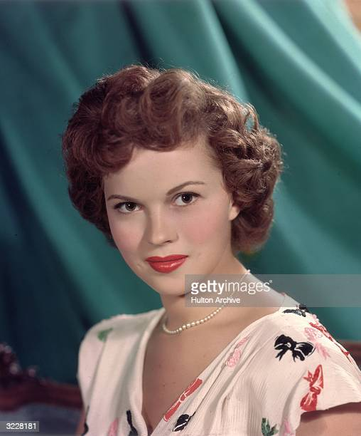Headshot studio portrait of American actor Shirley Temple in front of a green backdrop wearing a short sleeve white blouse with a colored bows...