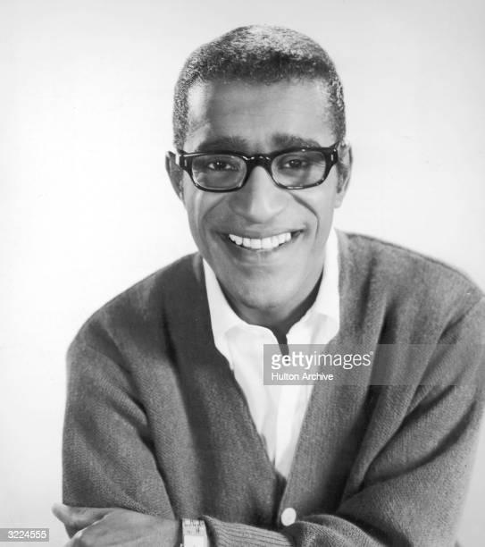 Headshot studio portrait of American singer actor and dancer Sammy Davis Jr wearing eyeglasses and a cardigan sweater