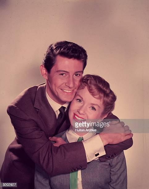 Headshot studio portrait of married American singer/actors Eddie Fisher and Debbie Reynolds; Fisher stands behind Reynolds, his arms around her...