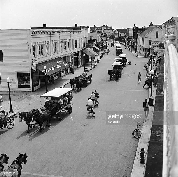 Horse drawn carts and bicyles passing along the main street of Mackinac Island Michigan where the use of cars is prohibited