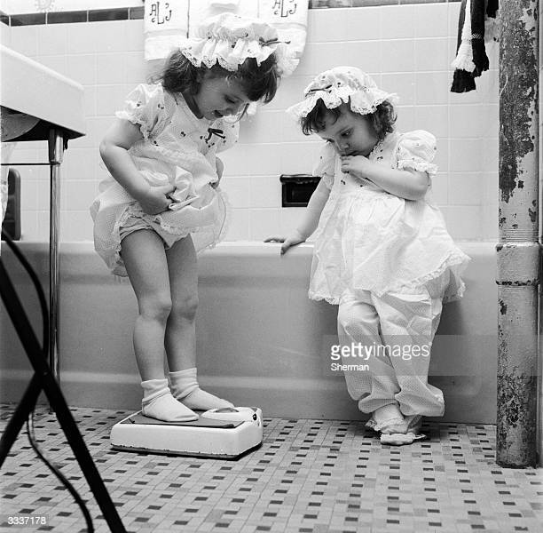 Identical twins Joan and Linda take turns to weigh themselves on the bathroom scales