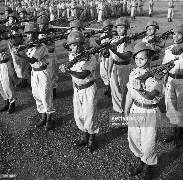 Indonesian soldiers with their guns on their shoulders