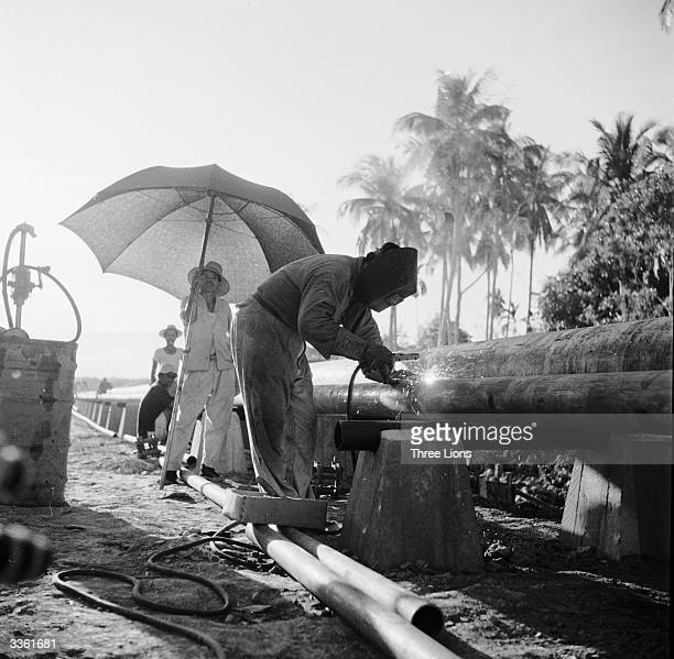 Indonesian welders working on pipe lines leading to an oil refinery on Sumatra