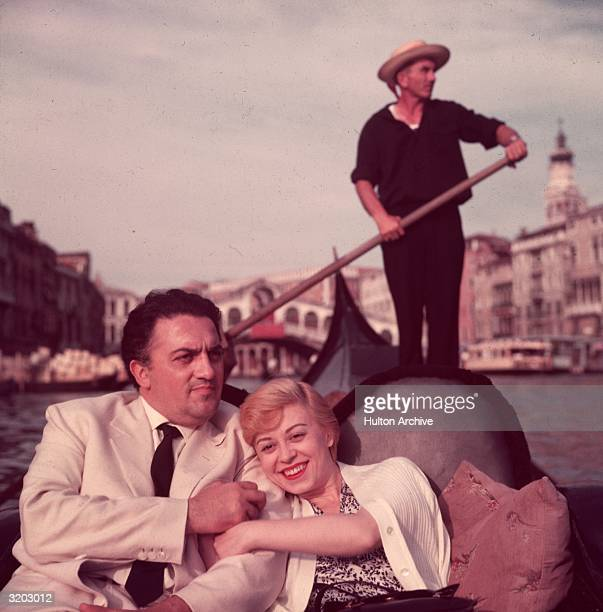 Italian film director Federico Fellini and his wife actor Giulietta Masina hold hands and smile while sitting in a gondola with a gondolier rowing in...