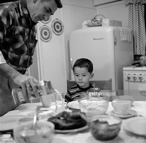 Jimmy Blake the adopted JapaneseAmerican son of American serviceman James Blake watches his father pour him one of his first glasses of milk at their...