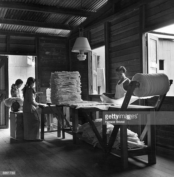 Labourers in a Malayan workshop cut up thin crepe fabric formed from pressed rubber latex into sheets and weigh them in piles