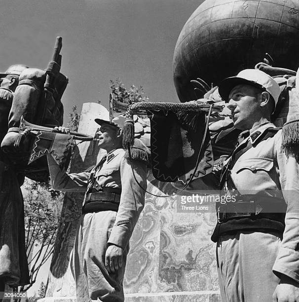 Legionnaires blowing their trumpets in front of the monument to the French Foreign Legion in the outpost at SidiBelAbbes where their headquarters are...