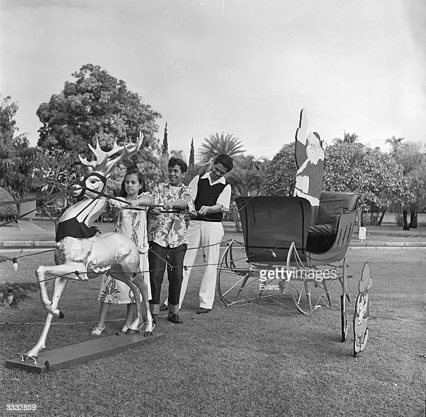 Locals in Honolulu amuse themselves with the Father Christmas, complete with sleigh and reindeer, that has been put in a park as a Christmas...