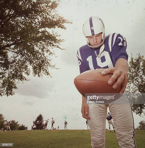 Low angle image of American football player John Unitas quarterback for the Baltimore Colts holding the ball in his left hand during practice on a...