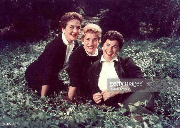 LR Group portrait of American singers and siblings Patti Andrews LaVerne Andrews and Maxene Andrews of the Andrews Sisters seated in a field of vines