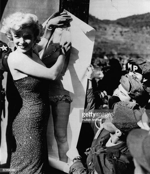 Marilyn Monroe the Hollywood film actress autographing a full sized picture of herself in a polka dot bikini for the troops