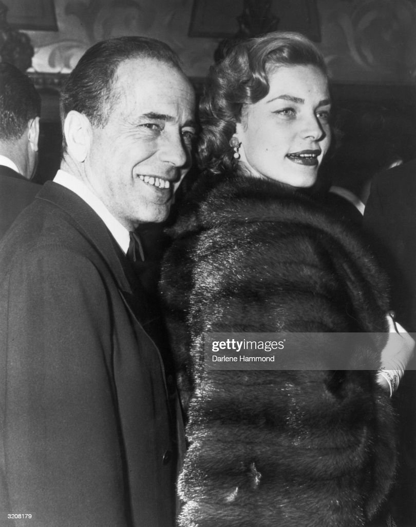 Married American actors Humphrey Bogart and Lauren Bacall laugh while standing together. Bacall wears a fur coat and white gloves.
