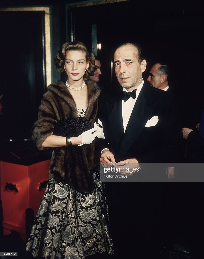 Married American actors Lauren Bacall and Humphrey Bogart (1899-1957) stand in a foyer after arriving together. Bacall wears a brocade dress, a mink wrap, and a pearl necklace. Bogart wears a tuxedo.