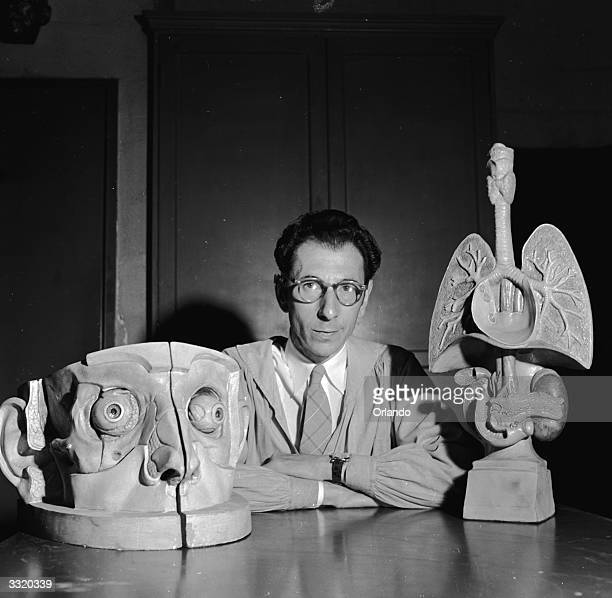 Medical sculptor Abram Belskie of New York Medical College and Flower and Fifth Avenue Hospitals with two of his creations a larger than life head...