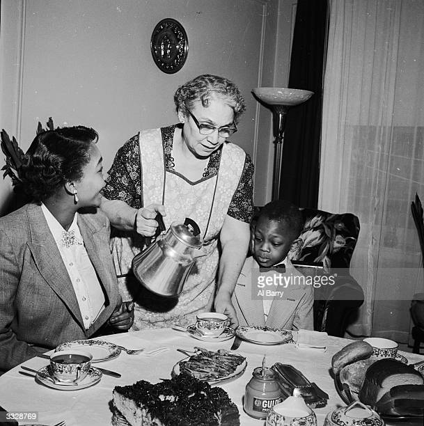 Mrs Thomas wife of Reverend Thomas and her son are seved tea by a white member of the congregation Reverend Thomas is the first black preacher to...