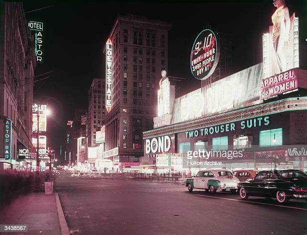 Neon signs for the Hotel Astor Loewe's State cinemas and the Bond clothing store at night in Times Square New York