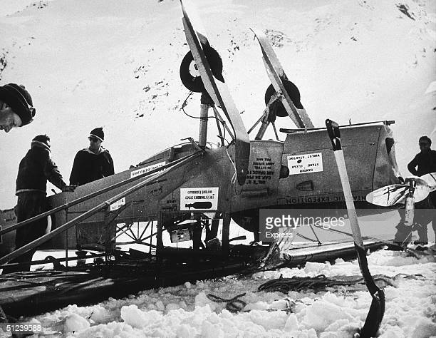Circa 1955 New Zealander explorer and mountaineer Sir Edmund Hillary with others by their overturned airplane on a snowcapped mountaintop in...