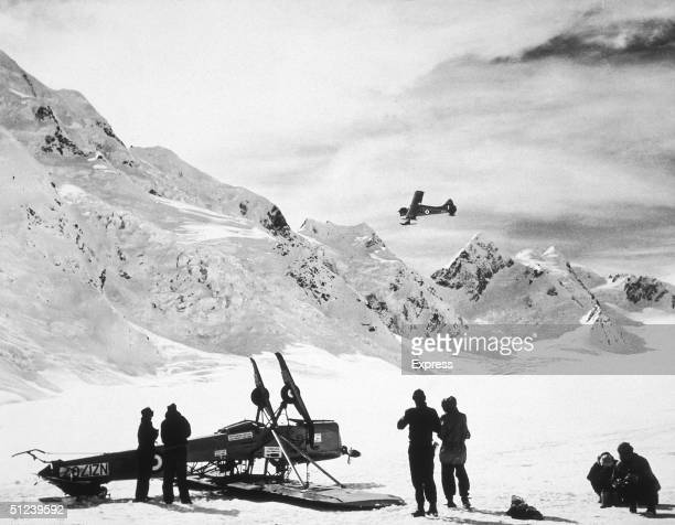 Circa 1955 New Zealander explorer and mountaineer Sir Edmund Hillary and others near an upturned airplane on a snowcapped mountaintop in Antarctica...